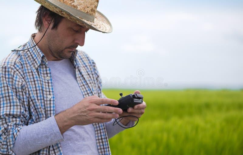Έξυπνη έννοια καλλιέργειας, αγρότης που χρησιμοποιεί τον κηφήνα στον τομέα στοκ φωτογραφία