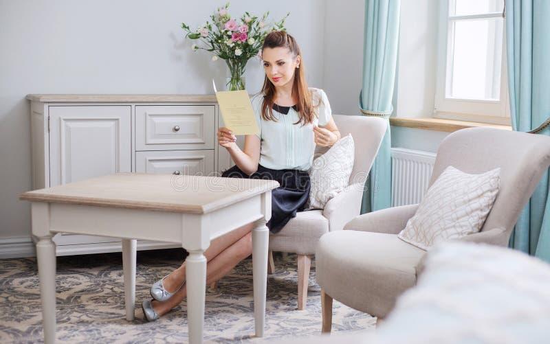 Έξυπνη γυναίκα που διαβάζει ένα φυλλάδιο στοκ φωτογραφίες