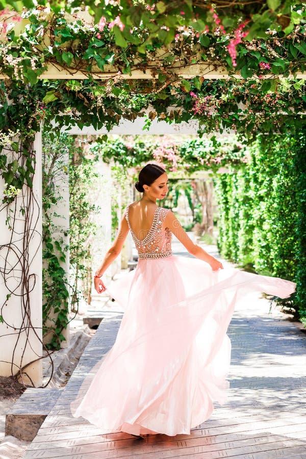 Έξυπνη γυναικεία νύφη σε ένα ρόδινο γαμήλιο φόρεμα στην τροπική αλέα κήπων Σύνοδος φωτογραφιών ημέρας γάμου, η κύρια ημέρα στοκ εικόνα με δικαίωμα ελεύθερης χρήσης