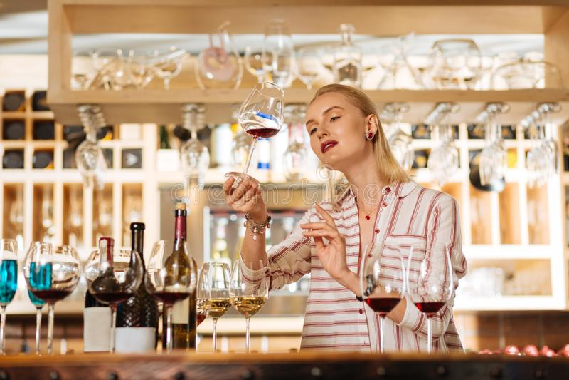 Έξυπνη ελκυστική γυναίκα που ελέγχει το χρώμα του κρασιού στοκ εικόνες