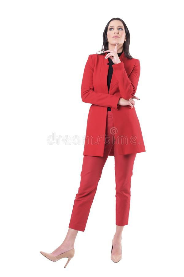 Έξυπνη νέα επιχειρησιακή γυναίκα στο κόκκινο κοστούμι με το δάχτυλο στο πηγούνι που σκέφτεται για τη λύση που ανατρέχει στοκ φωτογραφία