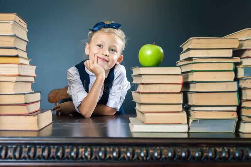Έξυπνη συνεδρίαση σχολικών κοριτσιών στον πίνακα με πολλά βιβλία στοκ εικόνες