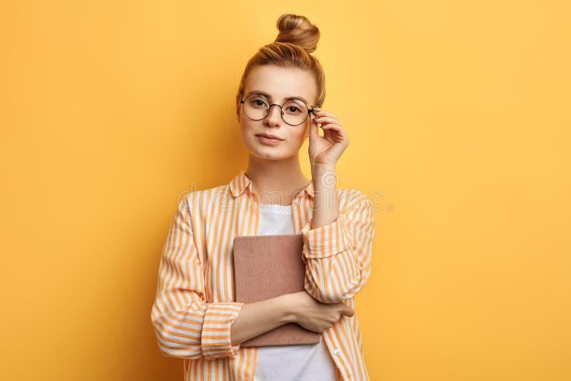 Έξυπνη τρομερή γυναίκα σχετικά με τα γυαλιά της και τοποθέτηση στη κάμερα στοκ φωτογραφία με δικαίωμα ελεύθερης χρήσης