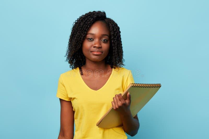 Έξυπνη όμορφη γυναίκα σπουδαστής afro που εξετάζει τη κάμερα στοκ εικόνες