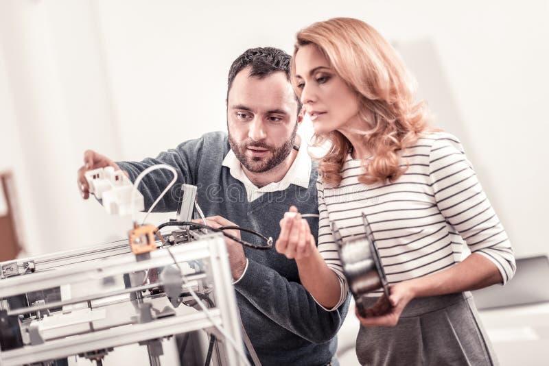 Έξυπνοι μηχανικοί που εξετάζουν τα τρισδιάστατα σχεδιαγράμματα εκτύπωσης εκτυπωτών στοκ εικόνες