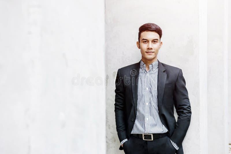 Έξυπνος ασιατικός επιχειρηματίας στο επίσημο κοστούμι, που εξετάζει τη κάμερα και Sm στοκ φωτογραφία με δικαίωμα ελεύθερης χρήσης