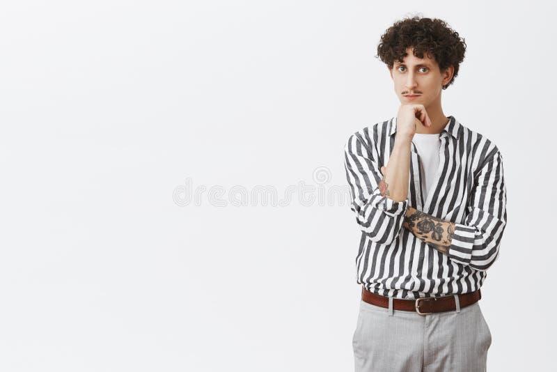 Έξυπνος και στοχαστικός νέος δημιουργικός αρσενικός επιχειρηματίας με το διαστισμένο βραχίονα moustache και σγουρή τρίχα καθιερών στοκ φωτογραφία με δικαίωμα ελεύθερης χρήσης