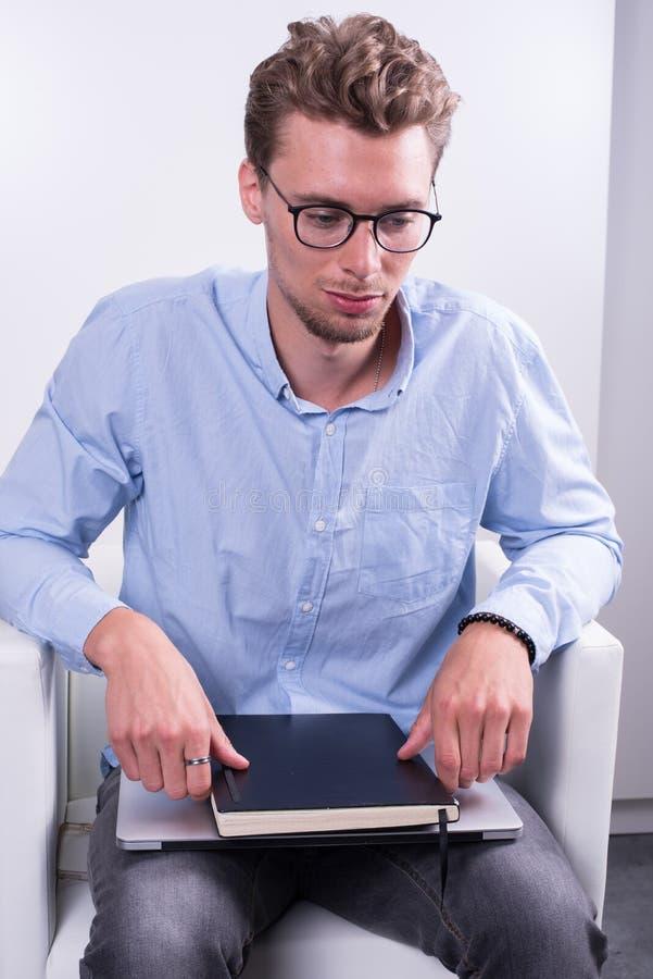 Έξυπνος νέος επαγγελματίας με το σημειωματάριο στα γόνατά του στοκ εικόνες