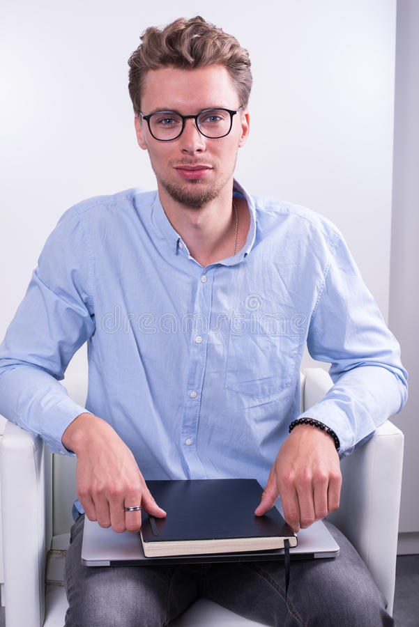 Έξυπνος νέος επαγγελματίας με το σημειωματάριο στα γόνατά του στοκ εικόνα με δικαίωμα ελεύθερης χρήσης