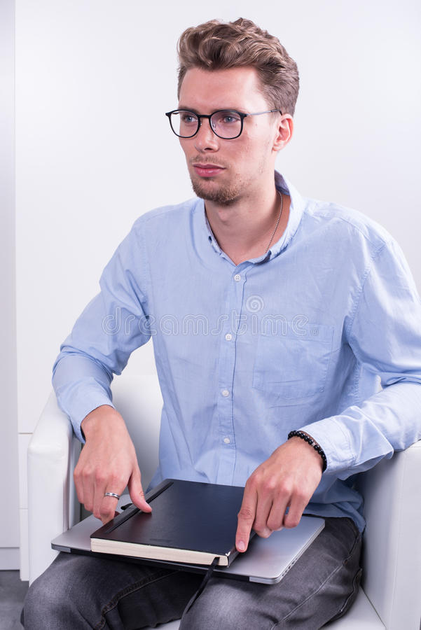 Έξυπνος νέος επαγγελματίας με το σημειωματάριο στα γόνατά του στοκ φωτογραφία με δικαίωμα ελεύθερης χρήσης