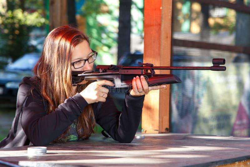 Έξυπνος πυροβολισμός κοριτσιών από το αεροβόλο πιστόλι στοκ εικόνα με δικαίωμα ελεύθερης χρήσης