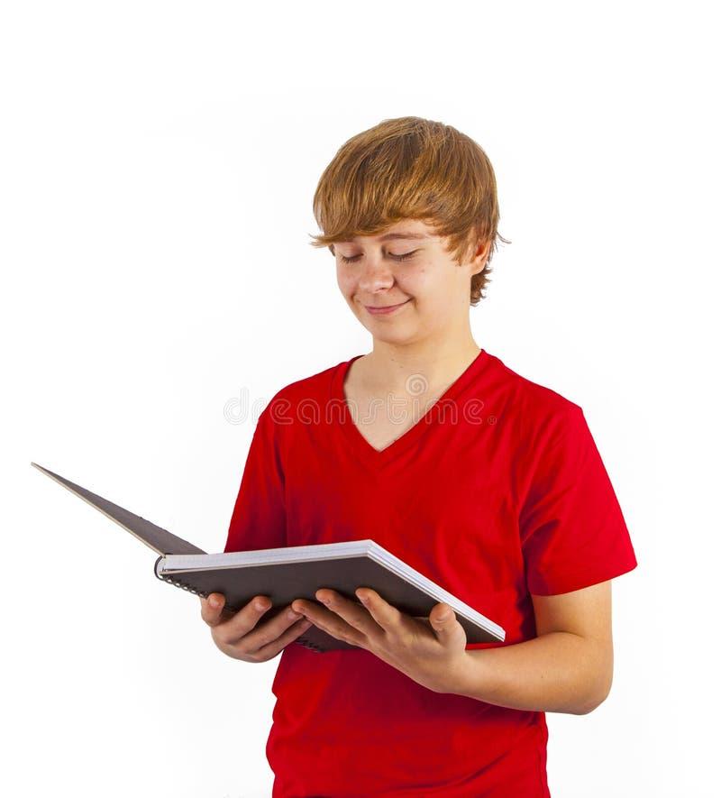 Έξυπνο αγόρι που διαβάζει σε βιβλίο στοκ εικόνα