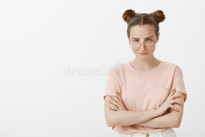 Έξυπνο αλαζονικό ευρωπαϊκό θηλυκό blogger στη μοντέρνη ρόδινη μπλούζα με τα κουλούρια hairstyle, κοιτάζοντας από κάτω από το μέτω στοκ εικόνες