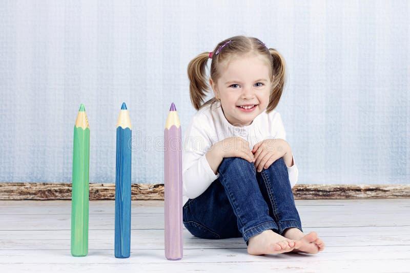 Έξυπνο μικρό κορίτσι με τα μεγάλα κραγιόνια στοκ εικόνα
