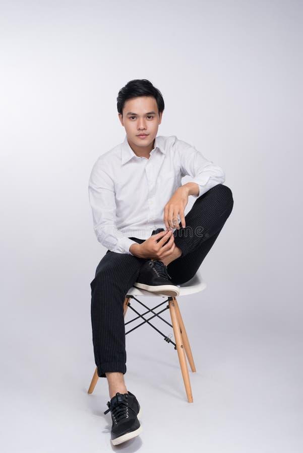Έξυπνο περιστασιακό ασιατικό άτομο που κάθεται στην καρέκλα, που θέτει εξετάζοντας στοκ φωτογραφίες με δικαίωμα ελεύθερης χρήσης