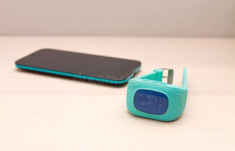 Έξυπνο ρολόι ΠΣΤ μωρών με την επίδειξη επάνω και ένα έξυπνο τηλέφωνο στοκ φωτογραφίες