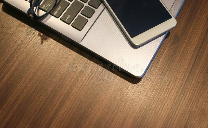 Έξυπνο τηλέφωνο και έννοια Teachnology: Τοπ διάστημα αντιγράφων άποψης για την κενή κενή οθόνη στο φορητό προσωπικό υπολογιστή στ στοκ εικόνες