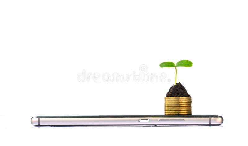 Έξυπνο τηλέφωνο με το σωρό των νομισμάτων και του σποροφύτου στην κορυφή στοκ φωτογραφία με δικαίωμα ελεύθερης χρήσης
