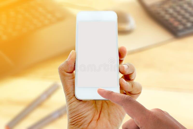 Έξυπνο τηλέφωνο οθόνης λαβής και αφής χεριών στο γραφείο γραφείων στοκ εικόνες με δικαίωμα ελεύθερης χρήσης
