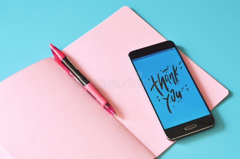 Έξυπνο τηλέφωνο που η επίδειξη ευχαριστεί σας και σημειώσεων το βιβλίο στοκ φωτογραφία με δικαίωμα ελεύθερης χρήσης