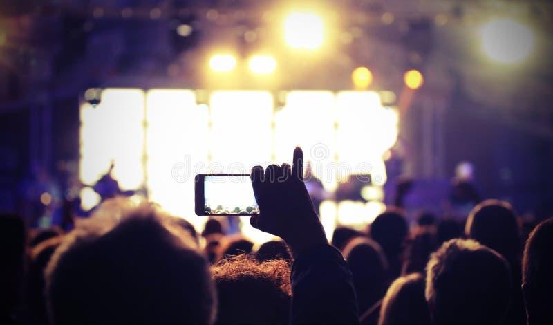 έξυπνο τηλέφωνο σε ετοιμότητα κατά τη διάρκεια μιας ζωντανής συναυλίας με τον τρύγο που τονίζεται στοκ φωτογραφίες