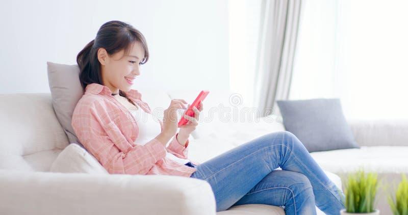 Έξυπνο τηλέφωνο χρήσης γυναικών ευτυχώς στοκ φωτογραφίες