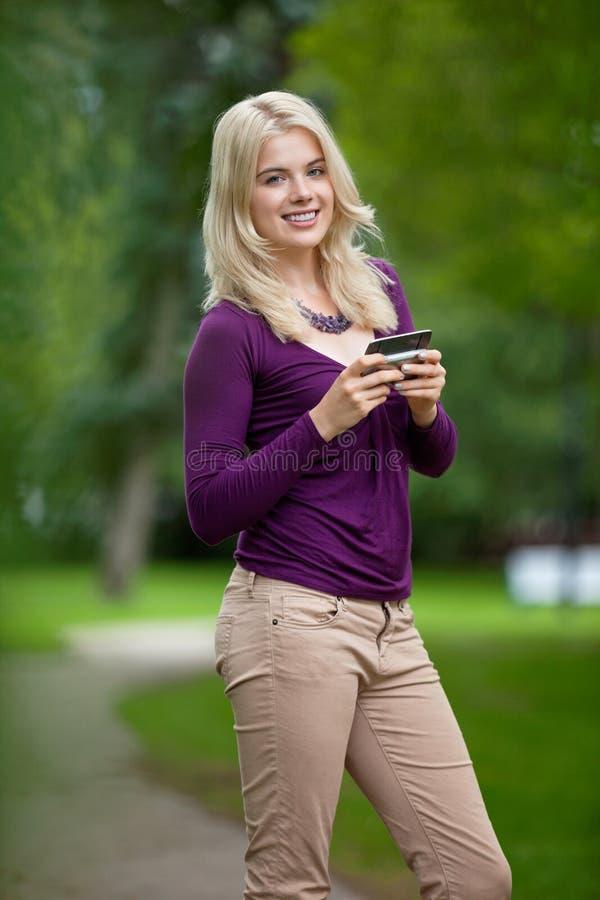 Έξυπνο τηλέφωνο εκμετάλλευσης γυναικών στο πάρκο στοκ εικόνες