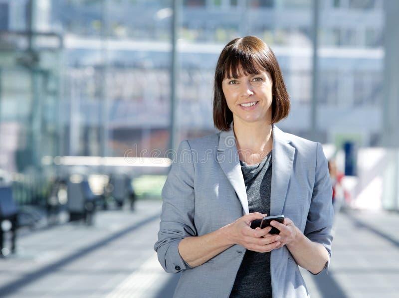 Έξυπνο τηλέφωνο κυττάρων εκμετάλλευσης επιχειρησιακών γυναικών στοκ εικόνες