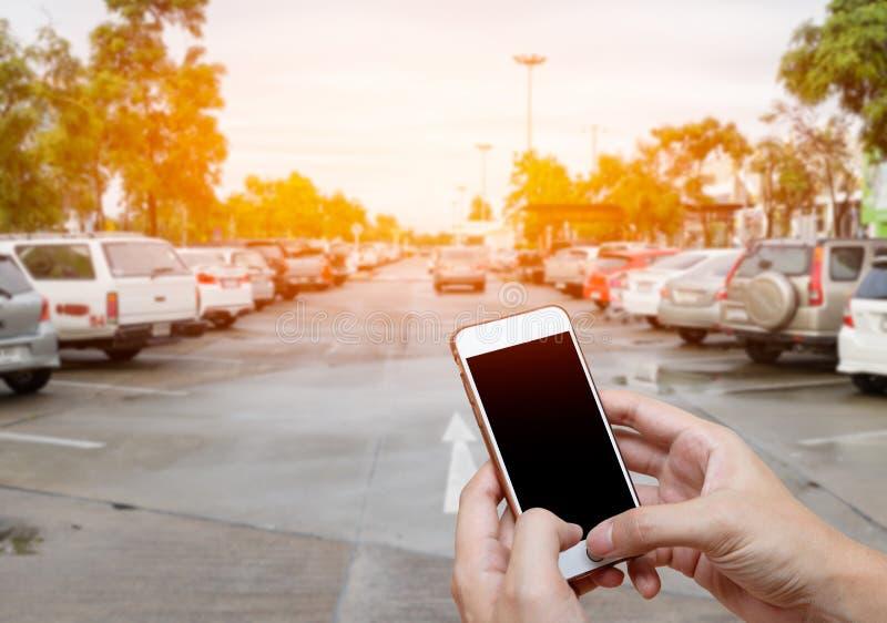 Έξυπνο τηλέφωνο που παρουσιάζει κενή οθόνη στο χέρι ατόμων με το πάρκο αυτοκινήτων θαμπάδων στοκ εικόνα με δικαίωμα ελεύθερης χρήσης