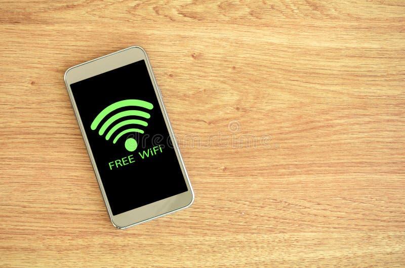 Έξυπνο τηλέφωνο στο ξύλινο υπόβαθρο με το ελεύθερο σημάδι Wifi στοκ εικόνες