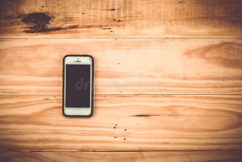 Έξυπνο τηλέφωνο στο ξύλινο υπόβαθρο ελεύθερη απεικόνιση δικαιώματος