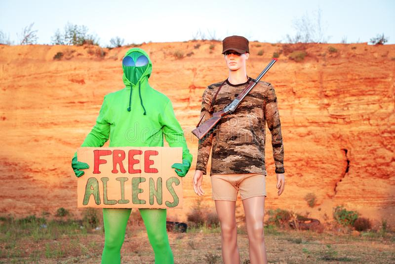 Έξω στην έρημο Γιούτα, δύο άνδρες ένας στρατιωτικός μανεκέν δεύτερος εξωγήινος, στο φόντο των βουνών που κρατούν πινακίδα στοκ εικόνες με δικαίωμα ελεύθερης χρήσης