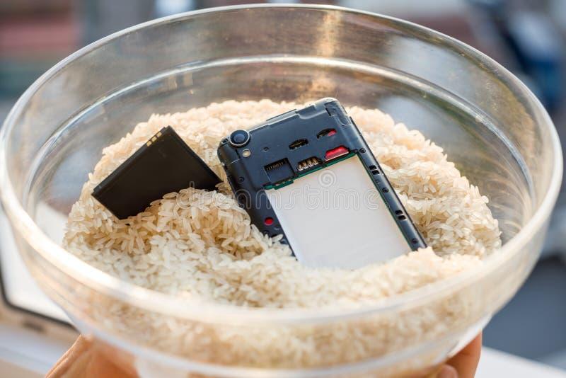 Έριξε το τηλέφωνό σας στο νερό - η αποτύπωση είναι ρύζι στοκ εικόνα