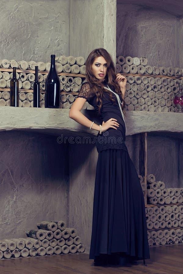 Έρχομαι-προς τα εδώ γυναίκα στο σεξουαλικό φόρεμα βραδιού στο κελάρι κρασιού πολυτέλεια στοκ εικόνα
