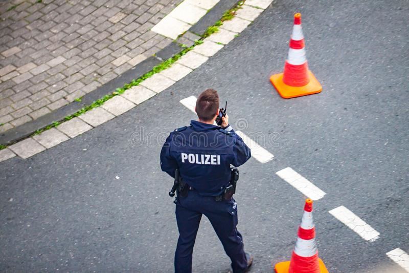 Έσσεν, Γερμανία - 29 Απριλίου 2019: Άτομο αστυνομίας που επικοινωνεί walkie-talkie στοκ εικόνες