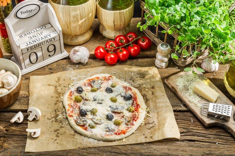 Έτοιμη πίτσα με τα φρέσκα συστατικά έτοιμα στο μαγείρεμα στοκ φωτογραφία