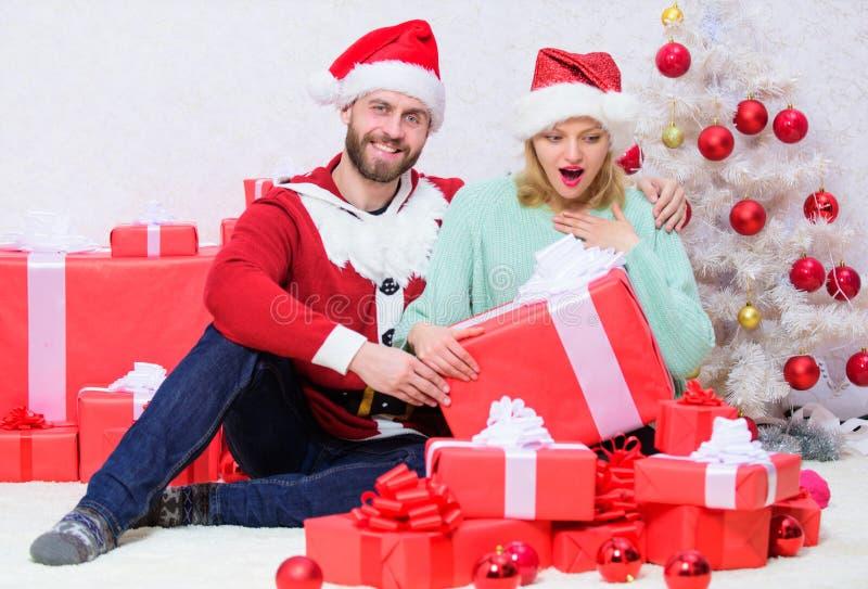 Έτοιμη σύζυγος έκπληξη Χριστουγέννων Ανοίγοντας χριστουγεννιάτικο δώρο Αγαπώντας υπόβαθρο χριστουγεννιάτικων δέντρων δώρων ζευγών στοκ εικόνες με δικαίωμα ελεύθερης χρήσης