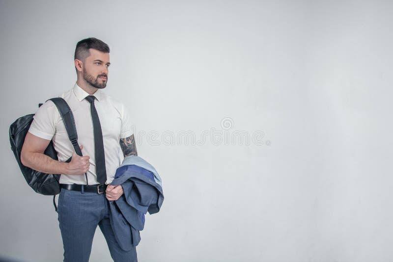 Έτοιμος να πάει Ο όμορφος νεαρός άνδρας στο άσπρο φέρνοντας δέρμα πουκάμισων και δεσμών τοποθετεί σε σάκκο στον ώμο και το κοίταγ στοκ φωτογραφία με δικαίωμα ελεύθερης χρήσης