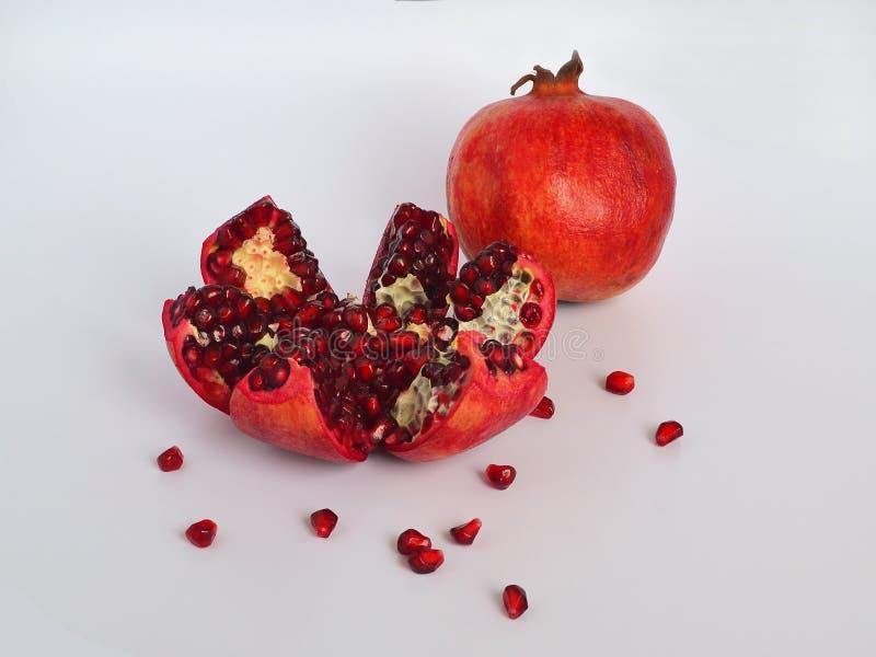Έτοιμος να φάει τα κόκκινα ώριμα juicy φρούτα ροδιών με τους σπόρους, υγιής έννοια κατανάλωσης σε ένα άσπρο υπόβαθρο στοκ φωτογραφίες με δικαίωμα ελεύθερης χρήσης