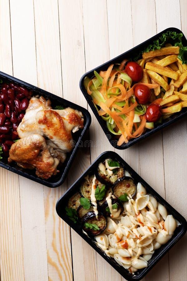 Έτοιμο γεύμα που τρώει στον ξύλινο πίνακα, κόκκινα φασόλια, ψημένα φτερά κοτόπουλου, μελιτζάνες, κολοκύθια στοκ φωτογραφία με δικαίωμα ελεύθερης χρήσης