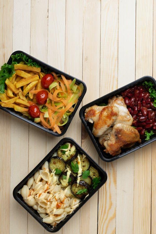 Έτοιμο γεύμα που τρώει στον ξύλινο πίνακα, κόκκινα φασόλια, ψημένα φτερά κοτόπουλου, μελιτζάνες, κολοκύθια στοκ εικόνες