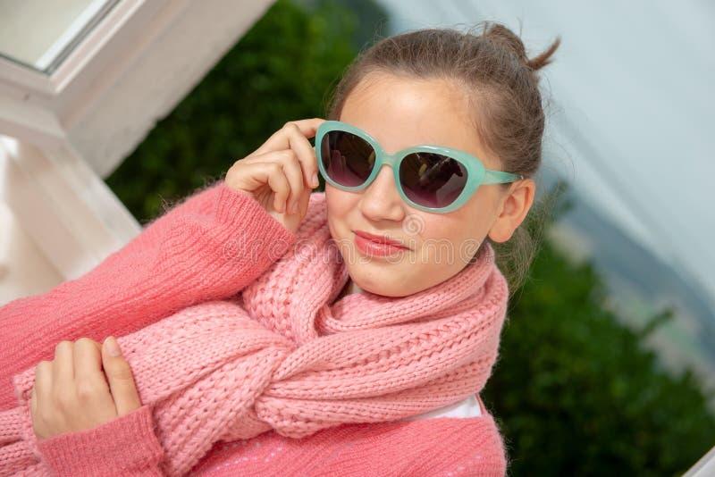 Έφηβη με τα ρόδινα ενδύματα και τα γυαλιά ηλίου κοντά στο παράθυρο στοκ φωτογραφία με δικαίωμα ελεύθερης χρήσης