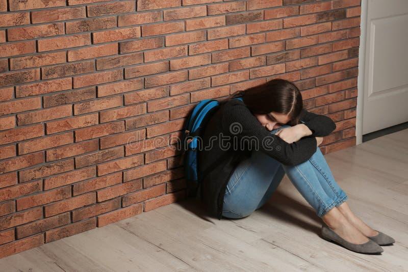 Έφηβη με τη συνεδρίαση σακιδίων πλάτης στο πάτωμα κοντά στον τοίχο στοκ εικόνες με δικαίωμα ελεύθερης χρήσης