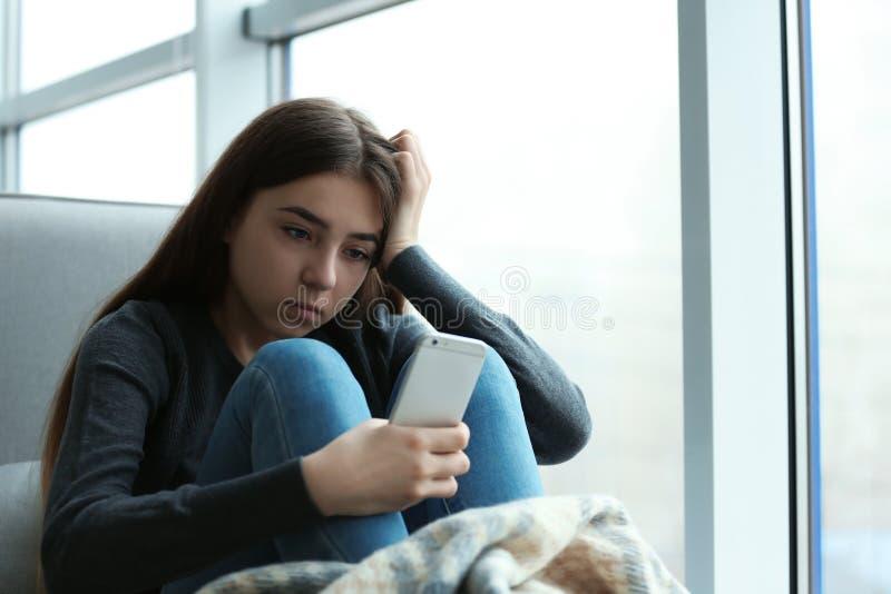 Έφηβη με τη συνεδρίαση smartphone στο παράθυρο στο εσωτερικό στοκ εικόνες με δικαίωμα ελεύθερης χρήσης