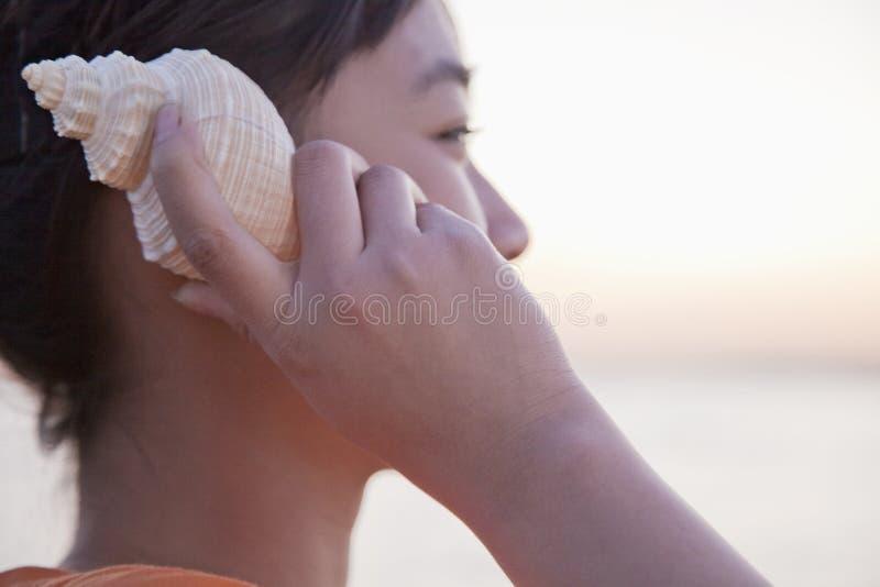 Έφηβη που ακούει το θαλασσινό κοχύλι, κινηματογράφηση σε πρώτο πλάνο στοκ εικόνα με δικαίωμα ελεύθερης χρήσης