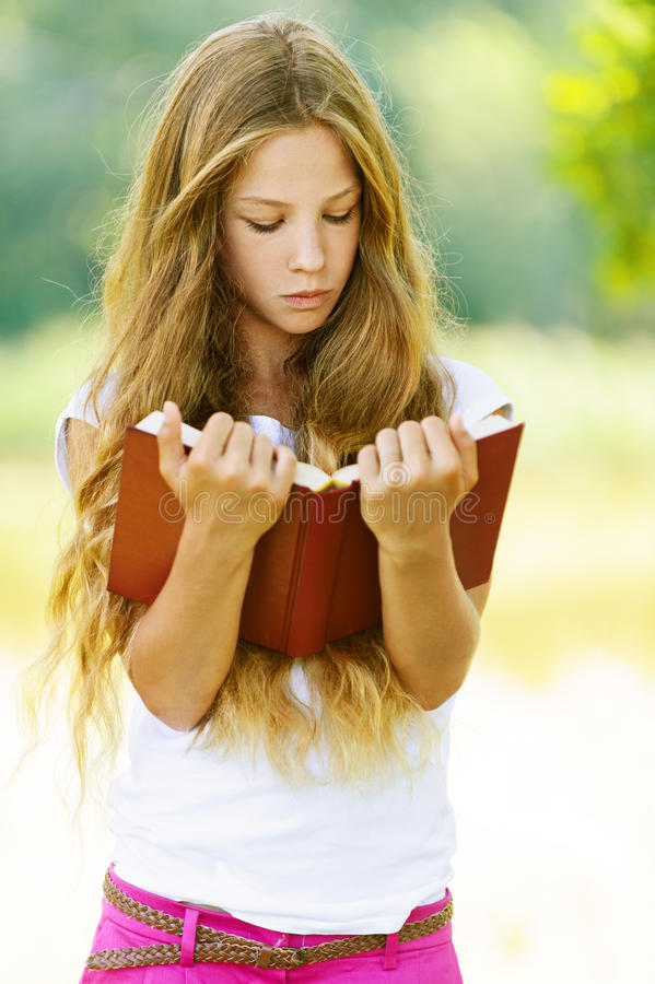 Έφηβη που διαβάζει το κόκκινο βιβλίο στοκ εικόνα με δικαίωμα ελεύθερης χρήσης