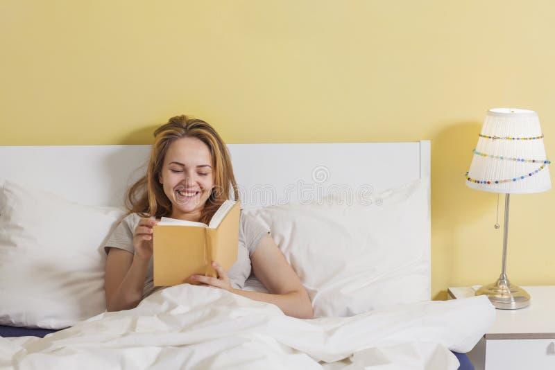 Έφηβη που διαβάζει ένα βιβλίο στο κρεβάτι στοκ φωτογραφίες με δικαίωμα ελεύθερης χρήσης