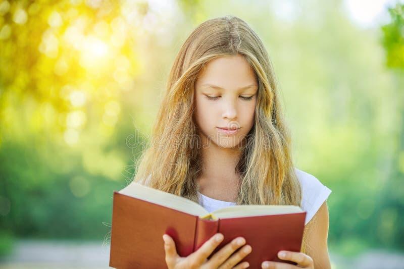 Έφηβη που διαβάζει το κόκκινο βιβλίο στοκ εικόνα