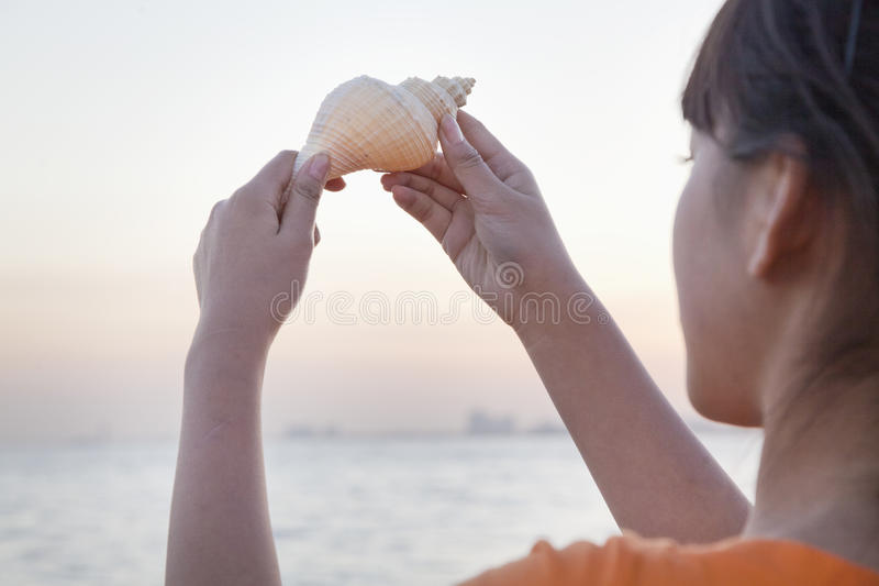 Έφηβη που κοιτάζει και που κρατά ψηλά το θαλασσινό κοχύλι στοκ εικόνες με δικαίωμα ελεύθερης χρήσης