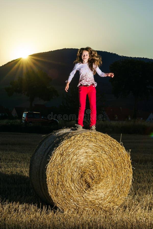 Έφηβη που πηδά από τη θυμωνιά χόρτου στοκ φωτογραφία με δικαίωμα ελεύθερης χρήσης